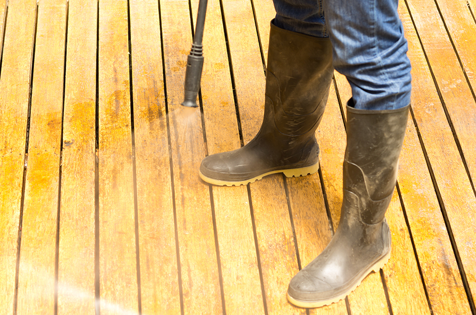 Man wearing rubber boots using low water pressure cleaner on wooden terrace surface.