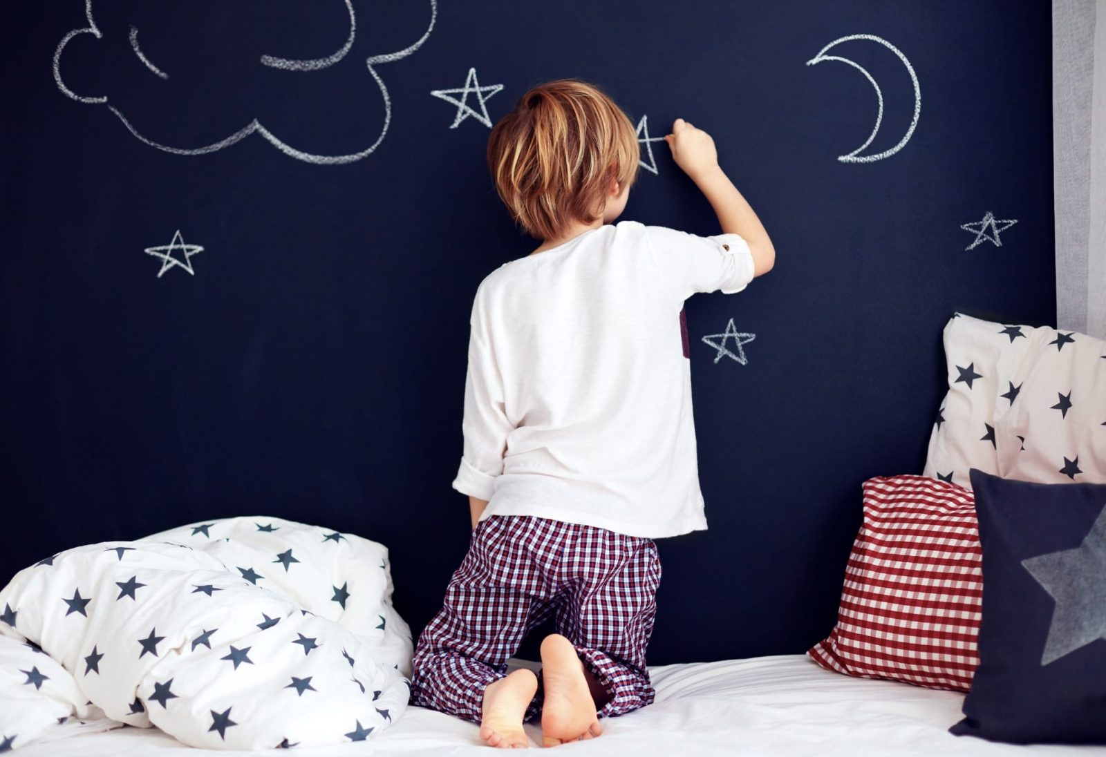 Child drawing on chalkboard