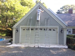 Painter on Ladder in Front of Garage in Barnstable